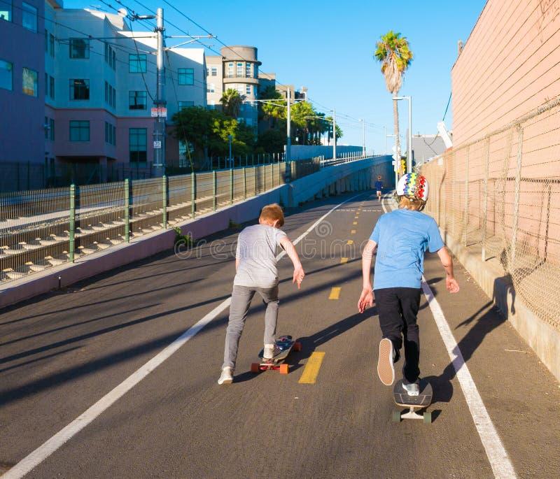 踩滑板在洛杉矶地铁自行车道路的男孩 免版税库存图片