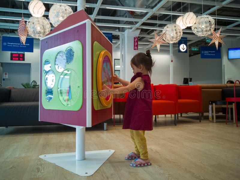 蹒跚学步的孩子在切拉斯的宜家店玩耍,在客户服务区等候 免版税库存照片