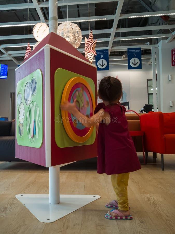 蹒跚学步的孩子在切拉斯的宜家店玩耍,在客户服务区等候 库存图片