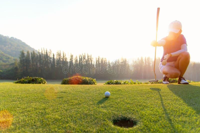 蹲下亚裔女子的高尔夫球运动员和在投入射击前学习绿色 免版税图库摄影