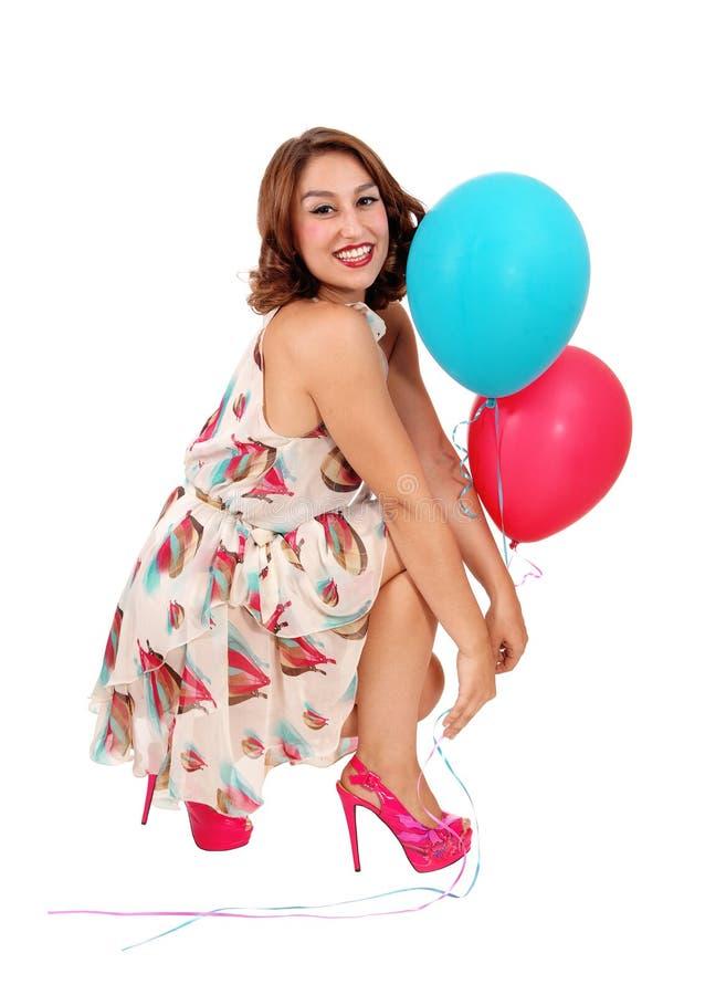 蹲下在与气球的地板上的妇女 免版税库存照片