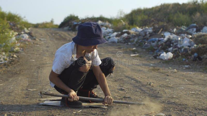 蹲下在垃圾填埋的肮脏的面对的男孩 库存照片