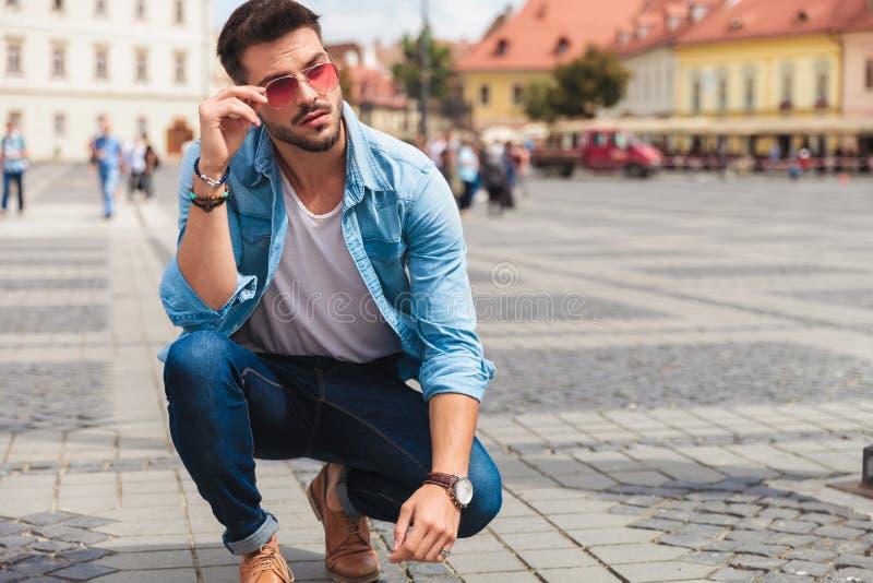 蹲下在城市的好奇偶然人修理红色太阳镜 库存图片