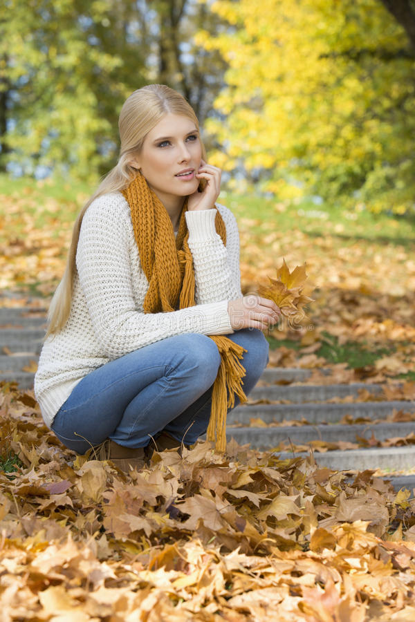 蹲下在步的全长体贴的少妇在公园 免版税库存图片