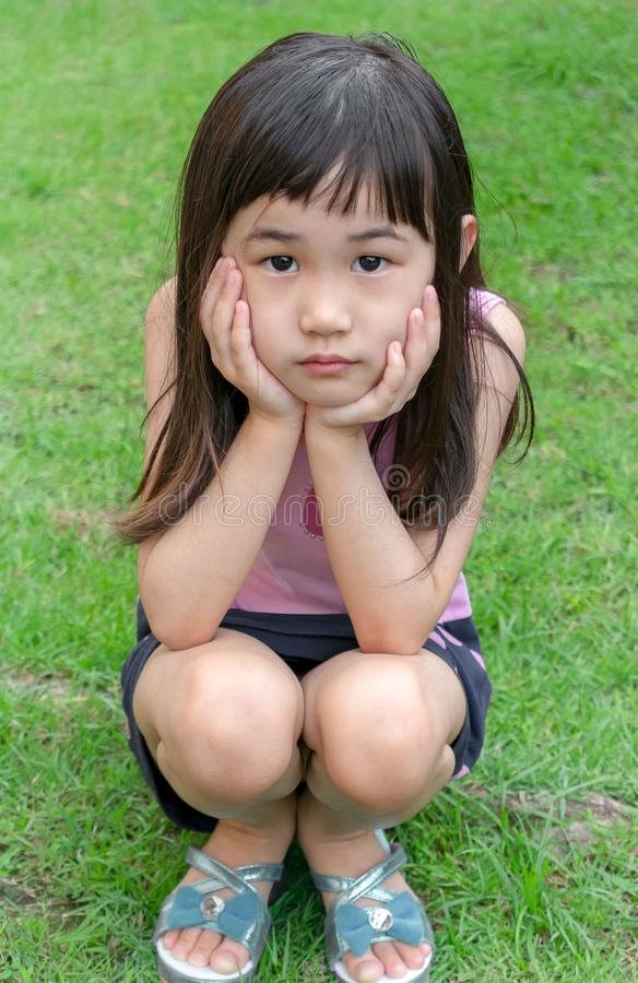 蹲下在草的一个年轻亚裔女孩的画象 免版税图库摄影