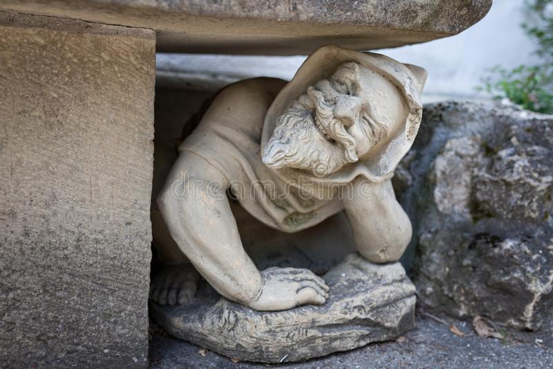 蹲下在长凳下的滑稽的人的雕象在庭院里 免版税库存图片
