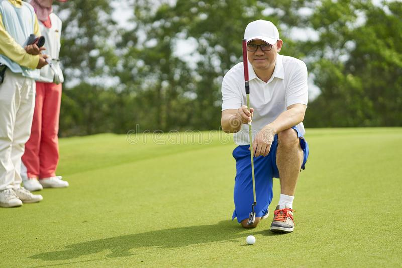蹲下在高尔夫球场的亚裔高尔夫球运动员瞄准和为投入做准备 免版税库存照片