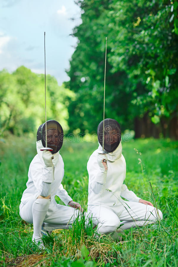 蹲下来与双刃剑的两名击剑者妇女指向  库存照片