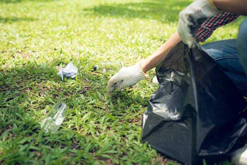 蹲下浪费和接它在容器袋子的年轻人 免版税图库摄影
