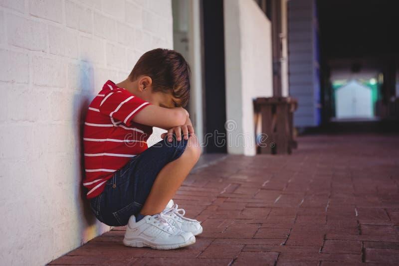蹲下由墙壁的沮丧的男孩侧视图 免版税库存图片