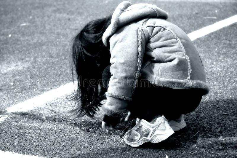 蹲下的女孩 库存图片