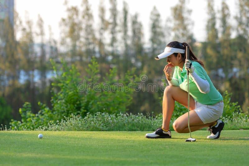 蹲下运动的亚裔女子的高尔夫球运动员和在投入射击前学习绿色在假期和假日 免版税库存照片