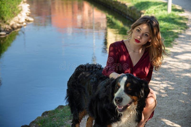 蹲与她的狗的美女的画象由小河 库存图片