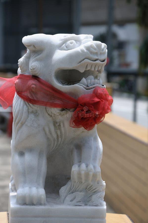 蹲中国监护人狮子佩带一条红色丝带的由白色石头制成在它的脖子上 免版税库存照片