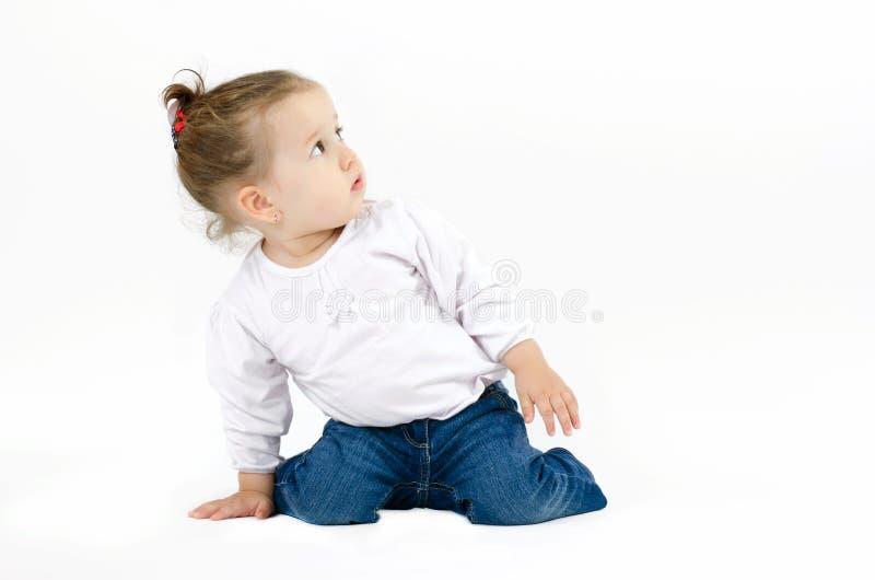 蹲在他的膝盖和倾斜单手的逗人喜爱的小女孩在查寻的地面上好奇地 库存图片