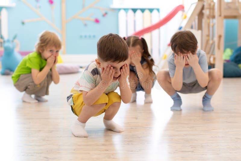 蹲在托儿的地板上,获得乐趣和打捉迷藏比赛的小组孩子,掩藏面孔用手 库存照片