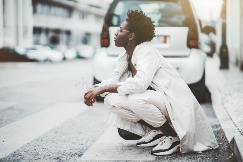 蹲在路边的非洲裔妇女 免版税库存照片