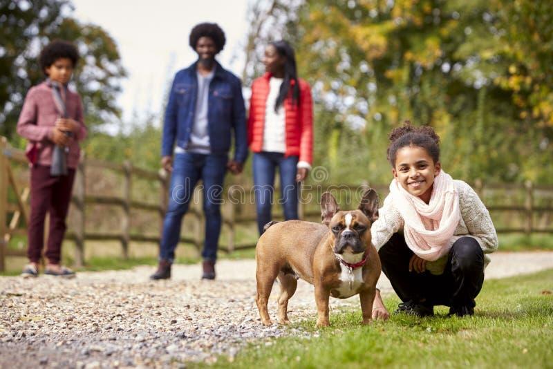 蹲混合的族种的女孩宠爱她的狗在家庭步行期间在看对照相机,低角度的乡下 免版税图库摄影