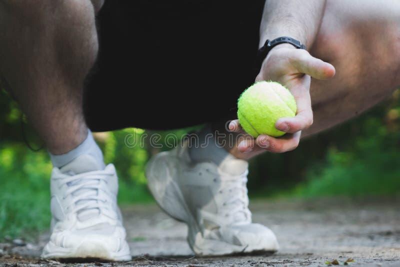 蹲着的男子手里拿着一个网球 库存图片