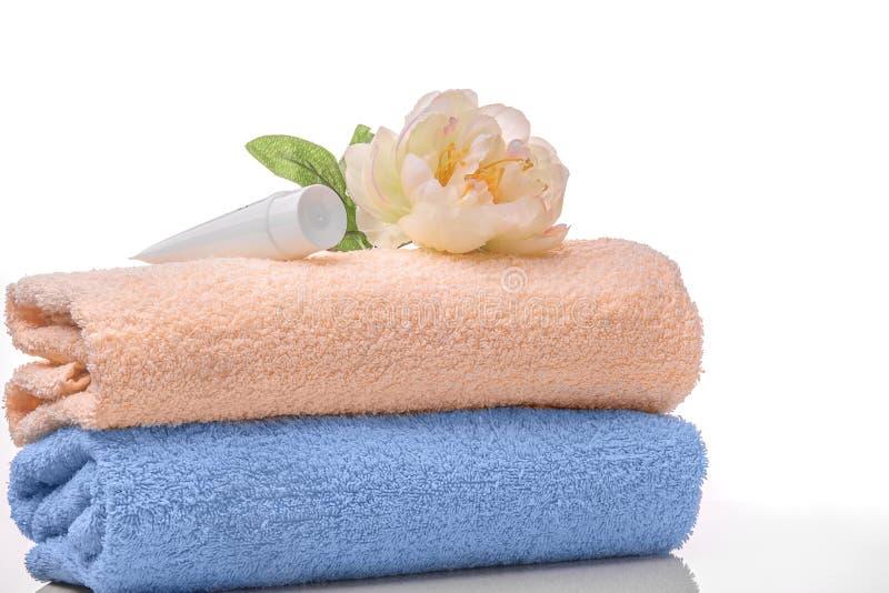 身体、奶油管和花的两块毛巾在一白色backg 免版税库存图片