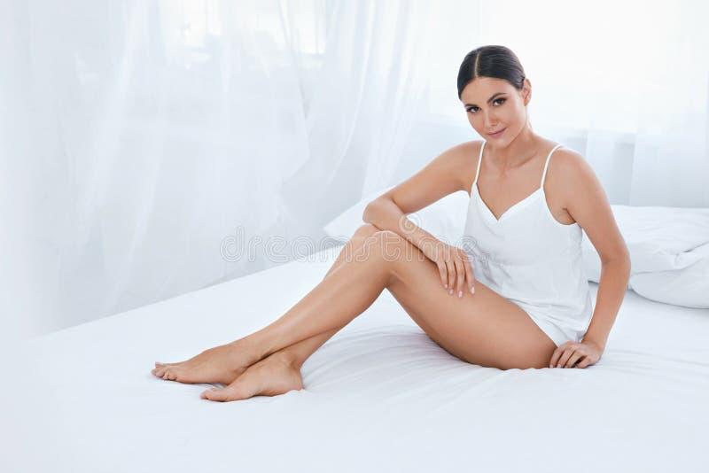 身体护肤 有长的腿和软的皮肤的妇女在白色 免版税图库摄影