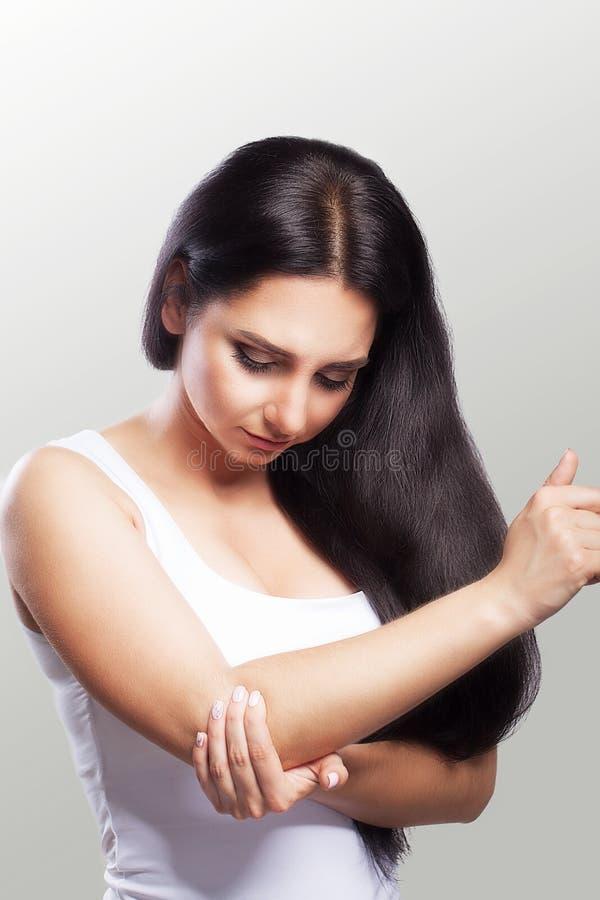 身体疼痛 感觉在手肘的妇女锐痛 美好的年轻女性痛苦画象从痛苦的感觉在胳膊,藏品的 库存照片