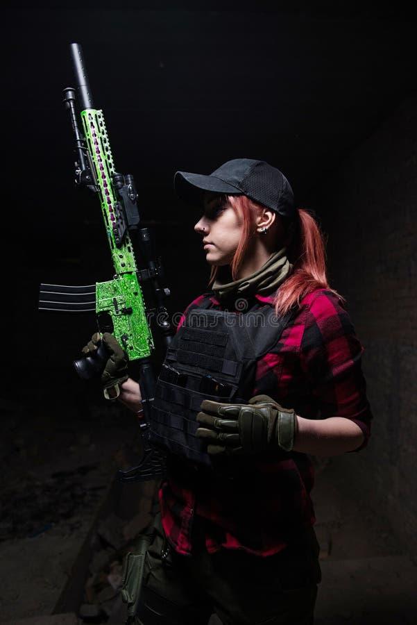 身体装甲的俏丽的年轻女人有枪的 库存图片