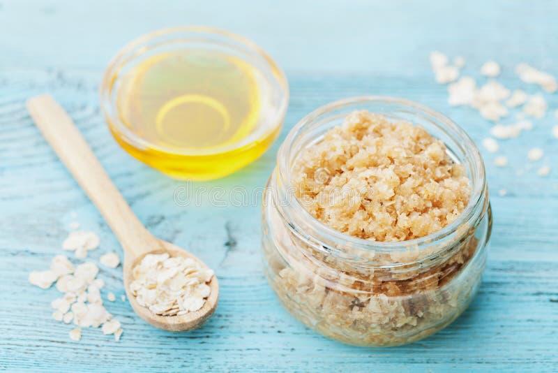身体洗刷燕麦粥、糖、蜂蜜和油在玻璃瓶子在蓝色土气桌上,自创化妆用品剥皮的和温泉 免版税图库摄影