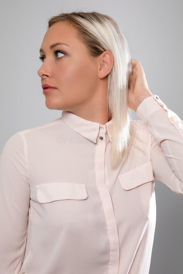 身穿粉色衬衫、留着头发的金发美女模特 免版税图库摄影