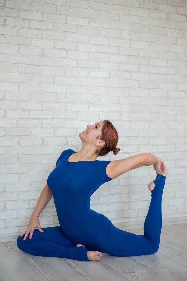 身穿蓝色连体服的红发女子在明亮的房间练瑜伽 女孩坐在鸽子的姿势上,向后弯 免版税库存照片