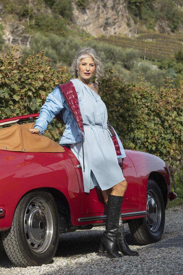 身穿蓝色连衣裙和羽绒夹克的女人,正倚在葡萄园中间的一辆古董红车上 免版税库存照片