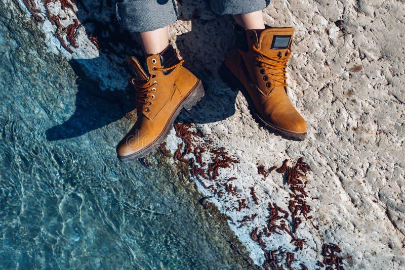 身穿黄色徒步靴子的无名女子坐在绿松石水附近的海岸上,俯视 探险,侦察,发现,探索 库存照片