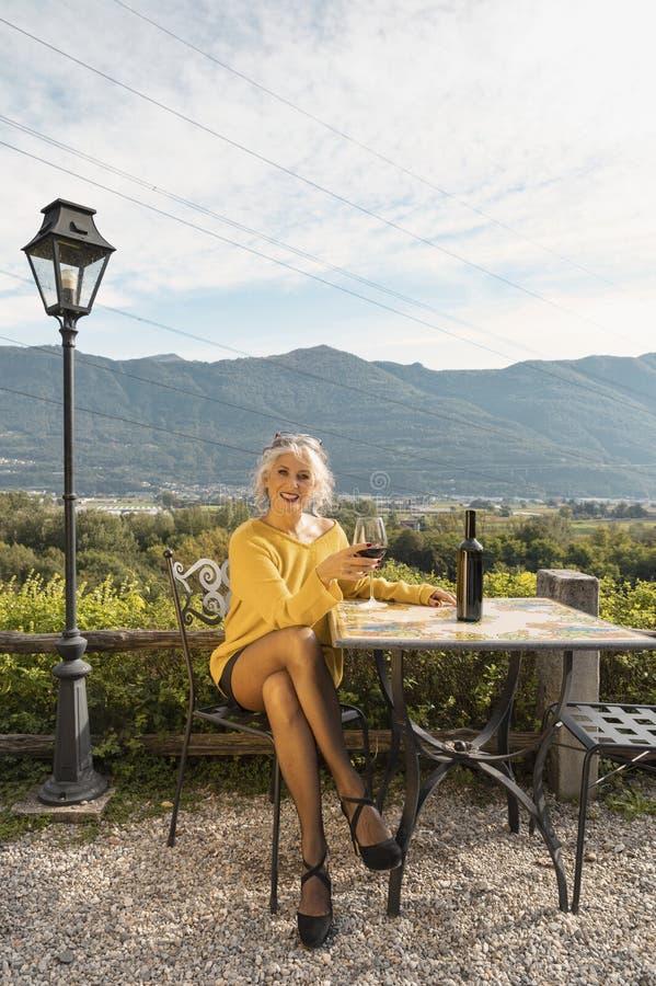 身穿黄色毛衣的女人坐着,喝着一杯红酒,背景是瑞士的山峦 库存照片