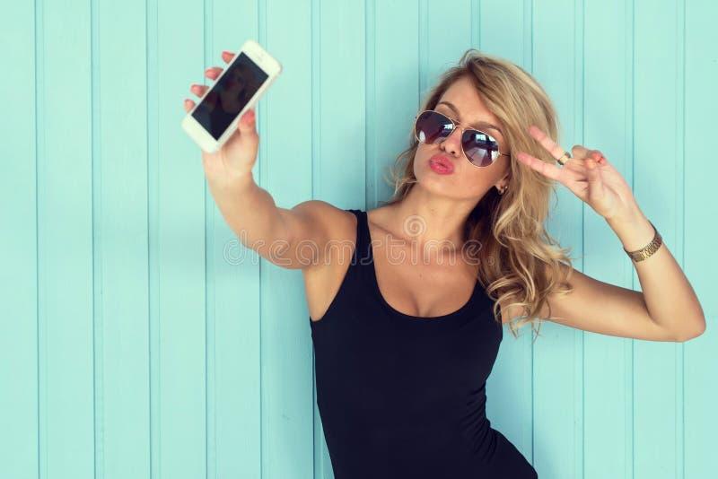 紧身衣裤的白肤金发的妇女与采取selfie智能手机的完善的身体定了调子instagram过滤器 免版税库存照片