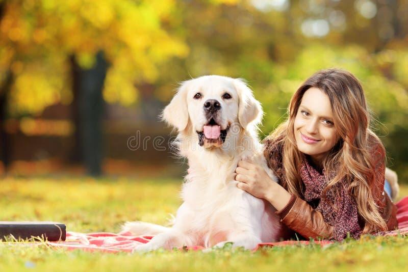 躺下与她的狗的年轻女性在公园 库存照片
