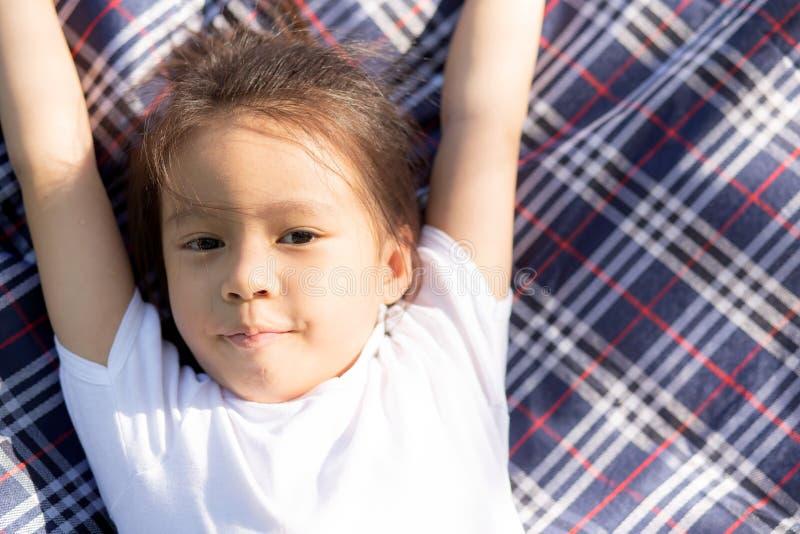 躺下和微笑在席子在公园,亚洲儿童画象的美丽的年轻亚裔女孩放松和休闲在假期 库存图片