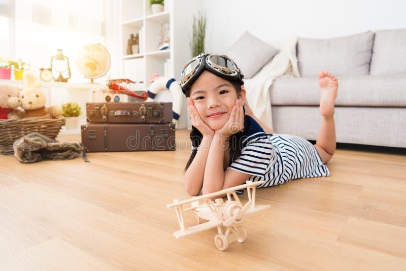 躺下在地板上的微笑的女性孩子飞行员 免版税图库摄影