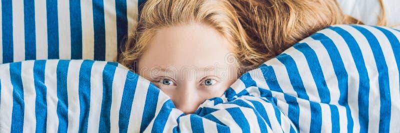 躺下在床和睡觉上的横幅美丽的少妇 不要得到足够的睡眠概念长的格式 图库摄影
