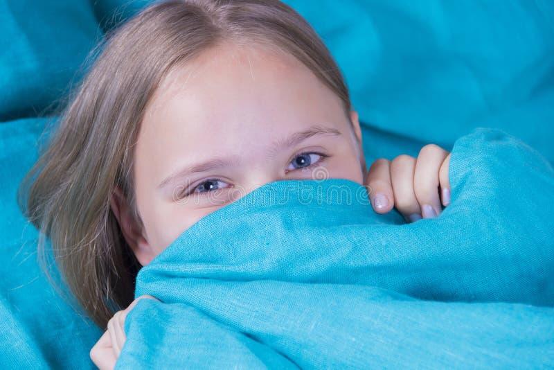 躺下在床和睡觉上的美丽的女孩 有开放眼睛的青少年的女孩用蓝色毯子盖她的面孔早晨 免版税库存照片