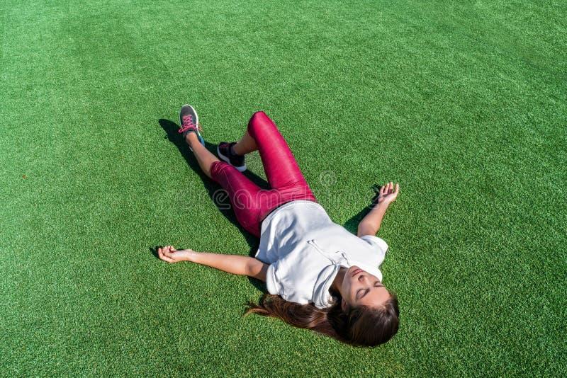 躺下在强烈的锻炼以后的疲乏的运动员 库存照片