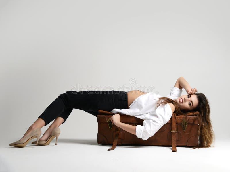 躺下在棕色减速火箭的白色衬衣的美丽的行家女孩 库存图片