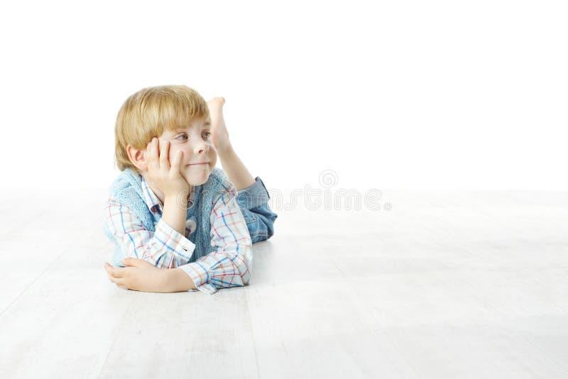 躺下在楼层上的小男孩,查看端 图库摄影