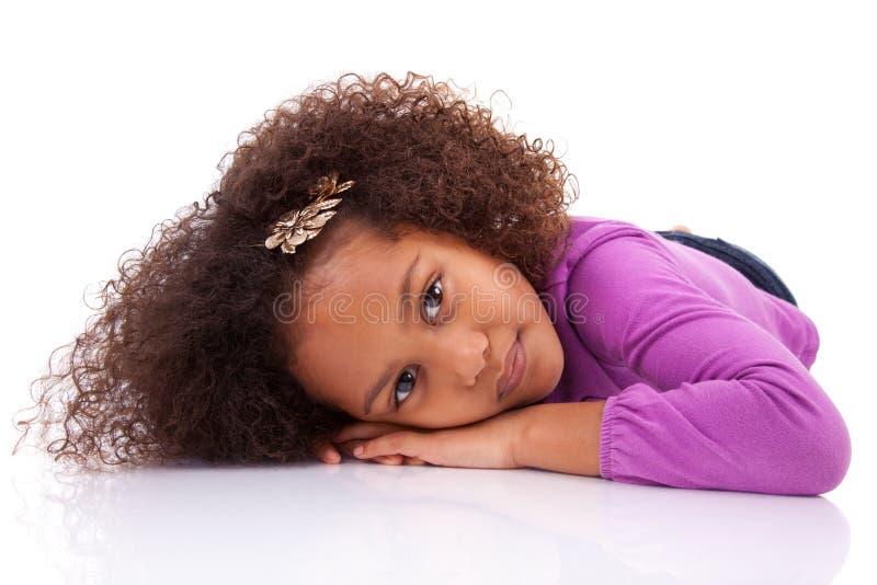 躺下在楼层上的非洲亚裔女孩 库存图片