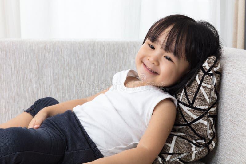 躺下在沙发的愉快的亚裔中国小女孩 库存照片