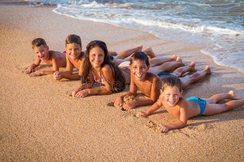 躺下在海滩的小组五个微笑的孩子 库存照片
