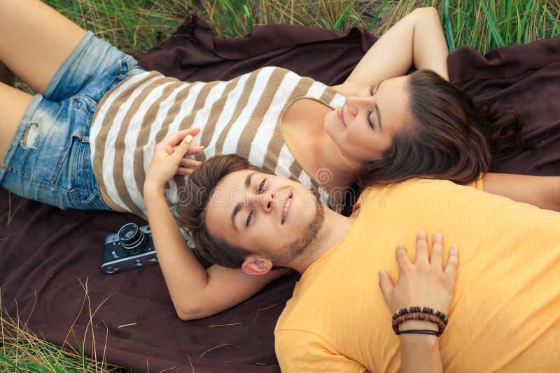 躺下在花卉领域的爱恋的夫妇在秋季公园,温暖 库存图片