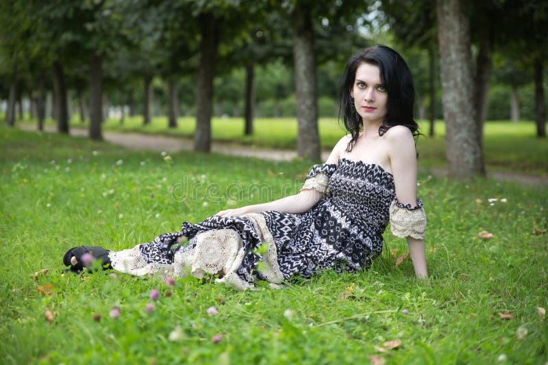 躺下在花草甸的美丽的女性在夏天绿色公园 库存图片