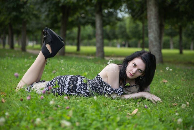 躺下在花草甸的美丽的女性在夏天绿色公园 图库摄影