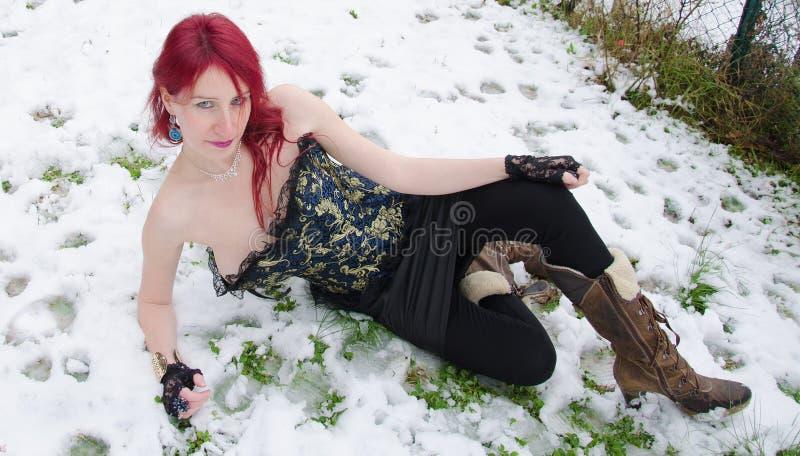 躺下在冻雪的妇女 库存图片
