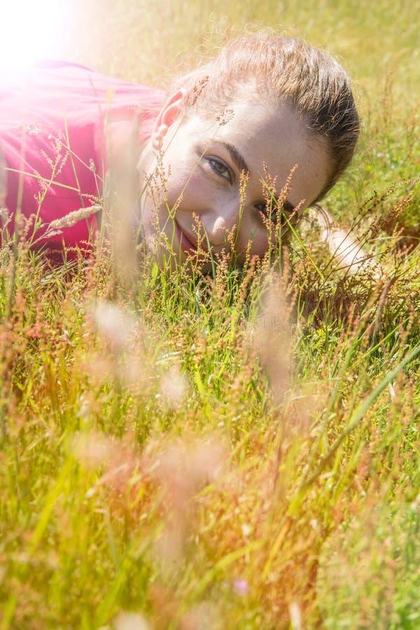躺下微笑的美丽的十几岁的女孩,看通过草 免版税图库摄影